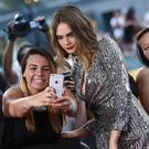 Actress Cara Delevingne poses with a fan at the premiere of Paper Towns in New York (AP)