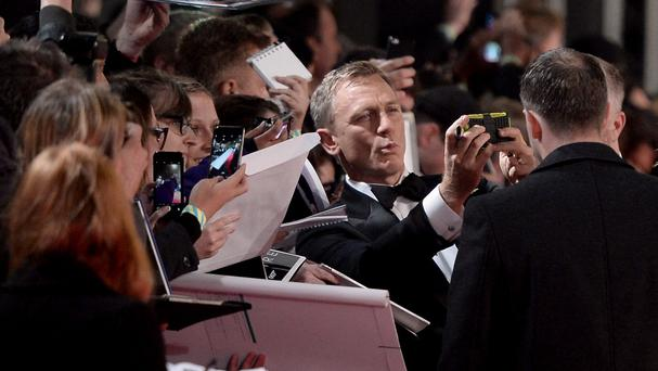 Daniel Craig takes a selfie with a fan attending the world premiere of Spectre, the new James Bond film
