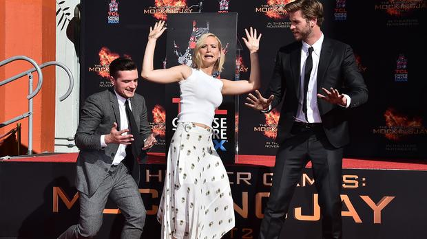 Josh Hutcherson, Jennifer Lawrence and Liam Hemsworth show off their hands after the LA ceremony (AP)