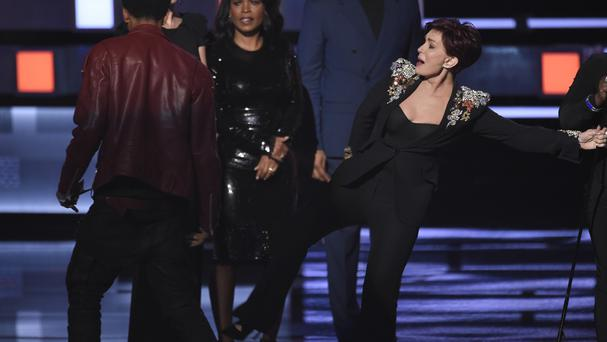 Sharon Osborne aims a kick at the man who invaded the stage at the People's Choice Awards (AP)