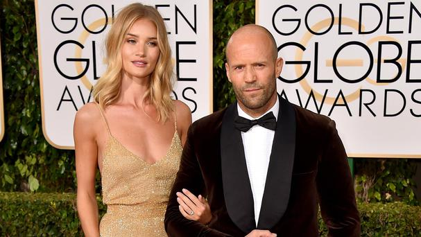 Rosie Huntington-Whiteley and Jason Statham sparked rumours of an engagement when they arrived at the Golden Globes (AP)