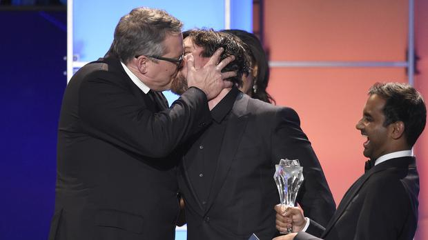 Adam McKay, left, kisses Christian Bale as he accepts the Critics' Choice Award for best comedy for The Big Short. (Invision/AP)