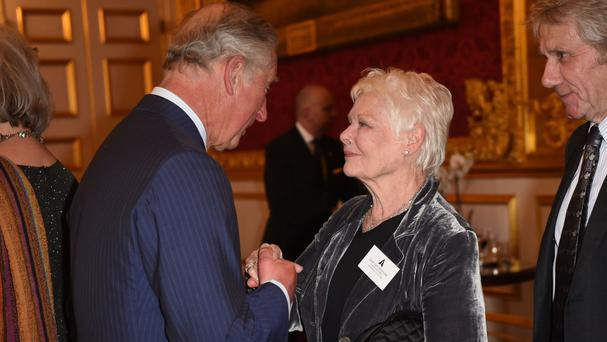 Dame Judi Dench greets the Prince of Wales during a reception for British Academy Award winners at St James's Palace