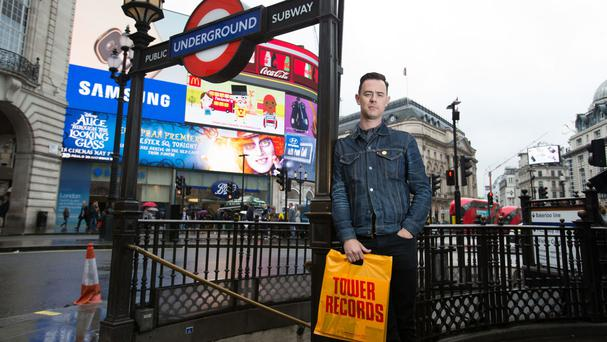 Colin Hanks holding a Tower Records bag at Piccadilly Circus ahead of his directorial debut with All Things Must Pass, a film that tells the story of Tower Records