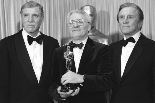 Triumphs: Actors Burt Lancaster (left), and Kirk Douglas (right) stand with Peter Shaffer, winner of the best adapted screenplay Oscar for Amadeus, during the Academy Awards in Los Angeles on March 25, 1985 Photo: AP