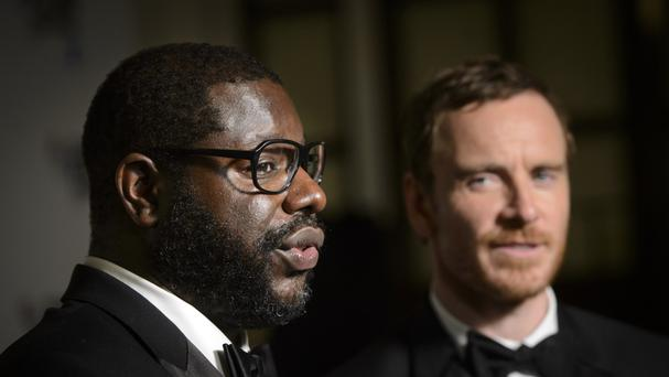Steve McQueen, winner of the BFI Fellowship Award, with presenter Michael Fassbender in the press room at the London Film Festival Awards, held at Banqueting House in London