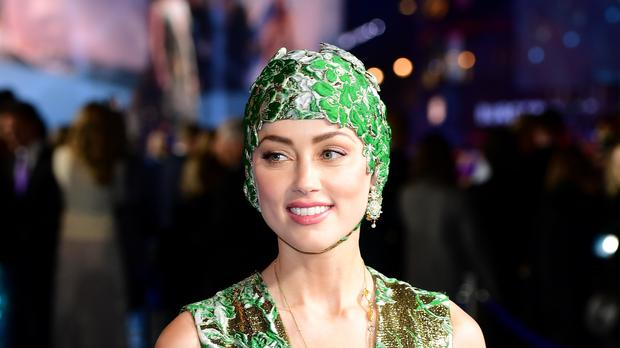 Amber Heard turned heads at the Aquaman premiere by arriving on the blue carpet wearing an emerald cap and gown (Ian West/PA Wire)