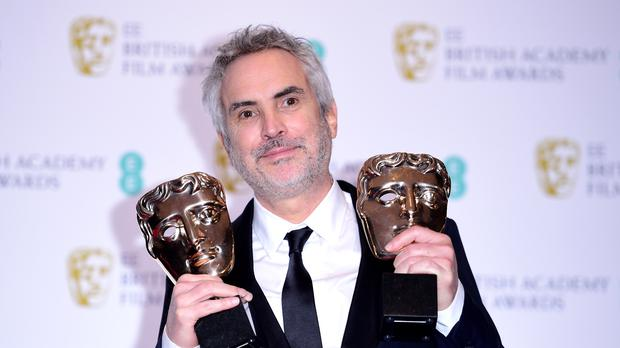 Alfonso Cuaron with his best film and best director Baftas (Ian West/PA)