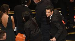 Rami Malek spoke with medical staff following a fall at the Oscars (Chris Pizzello/Invision/AP)