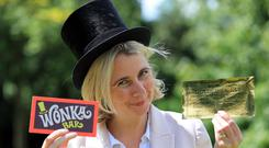 Auctioneer Catherine Southon holds the Golden Ticket and Wonka Bar props from the 1971 film Willy Wonka and The Chocolate Factory, which are going under the hammer (Gareth Fuller/PA)