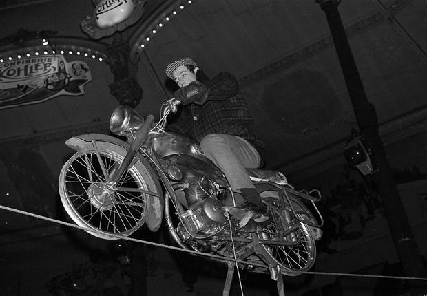 In a photograph from 1963, Jean-Paul Belmondo rehearses his motorcycle tightrope act at the Medrano Circus in Paris (Jacques Marqueton/AP)