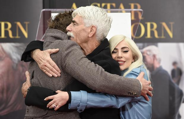 Bradley Cooper, left, and Lady Gaga, right, hug actor Sam Elliott as he was honoured in Hollywood (Chris Pizzello/Invision/AP)