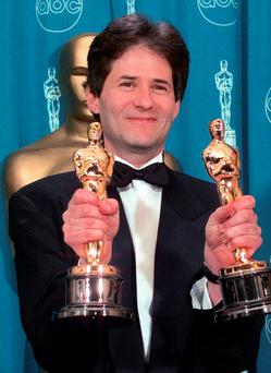 Composing titan: James Horner holds the Oscars he won for Original Song and Original Dramatic Score for Titanic at the 70th Academy Awards