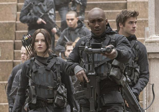 On war path: Mahershala Ali (centre), Jennifer Lawrence (left) and Liam Hemsworth (right) get tooled up in Mockingjay 2.