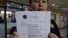 Philippine Bureau of Immigration deputy spokeswoman Dana Mengote holds a copy of the immigration lookout bulletin for Grammy award-winning singer Chris Brown (AP)