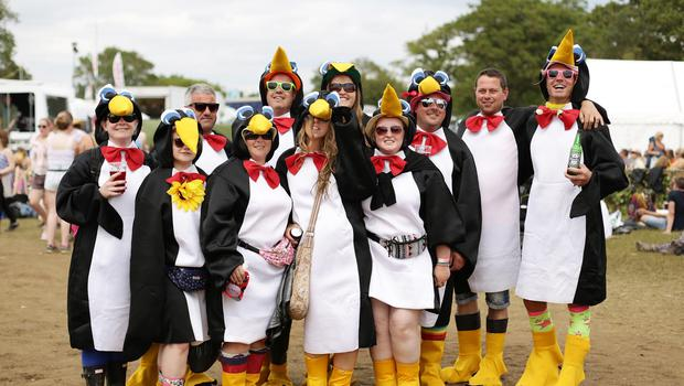 Festivalgoers in penguin outfits attend the Isle of Wight Festival