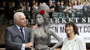 Amy Winehouse's parents Mitch and Janis next to a statue of their late daughter at the Stables Market, Camden Town, London.