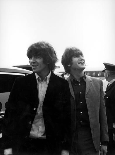 George Harrison and John Lennon depart London Airport in 1965 (PA)