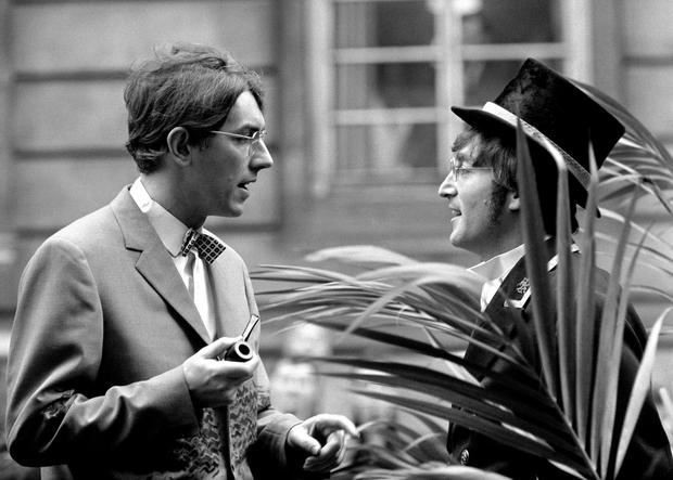 File photo dated 27/11/66 of Peter Cook (left) talking to John Lennon of The Beatles, in top hat and frock coat, standing guard among the palm trees placed there to adorn the entrance to a public lavatory in London, as he takes the part of a commissionaire hired out to give a running commentary about celebrities using the place. Friday October 9 marks The Beatles star's 80th birthday. PA Photo. Issue date: Thursday October 8, 2020. The musician was fatally shot by Mark David Chapman outside his Manhattan apartment in December 1980. See PA story SHOWBIZ Lennon. Photo credit should read: PA/PA Wire