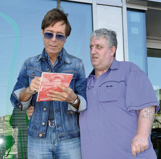 Cliff Richard signs an autograph for a fan outside Liffey Trust Studios in Dublin