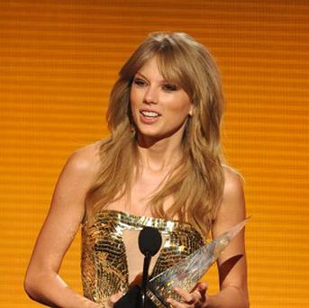 Taylor Swift accepts one of her awards at the American Music Awards (John Shearer/Invision/AP)