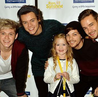 Four members of the boy band One Direction with young fan Livvie Ellis