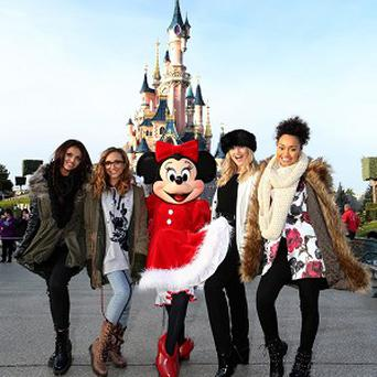 Little Mix posed with Minnie Mouse in front of the castle at Disneyland Paris