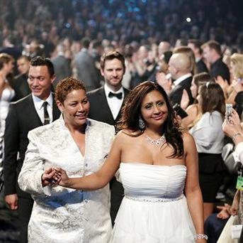 Audience members participate in a same sex wedding service during the Grammys (AP)