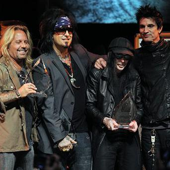 Vince Neil, Nikki Sixx, Mick Mars and Tommy Lee of Motley Crue pose together onstage at a tribute to the band in West Hollywood, California (AP)