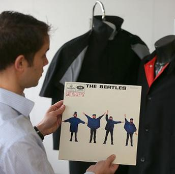 Auctioneer Paul Fairweather with jackets worn by George Harrison (right) and Ringo Starr on the cover of the Beatles album Help!