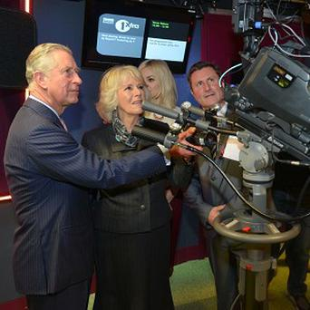 The Prince of Wales and the Duchess of Cornwall try out a camera during their visit to New Broadcasting House