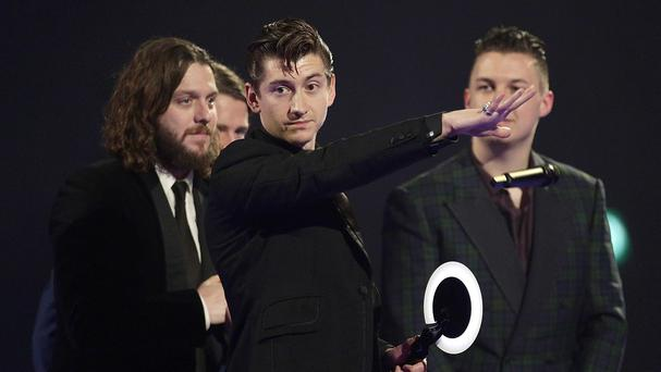 Alex Turner of the Arctic Monkeys on stage after winning an award during the 2014 Brits