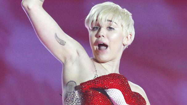 Miley Cyrus has said she wanted to perform during her allergic reaction in a suit to disguise the rash