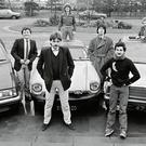 2fm DJs DJs, including Larry Gogan, Marty Whelan (centre) and Gerry Ryan (overcoat) pose with cars, in a shot taken for the RTE Guide in 1982