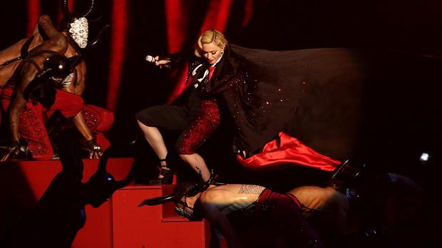 Madonna stumbles as her cape is pulled during the Brit Awards