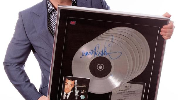 Robbie Williams with a multi-platinum award for the album I've Been Expecting You (Bonhams/PA)
