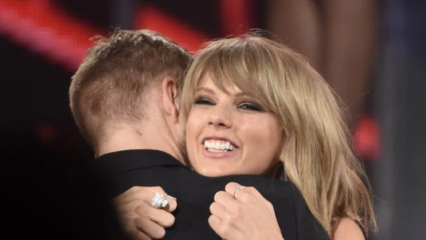 Taylor Swift hugs Calvin Harris at an awards ceremony. They have claimed number one spot in the Forbes list of the highest paid celebrity couples (Chris Pizzello/Invision/AP)