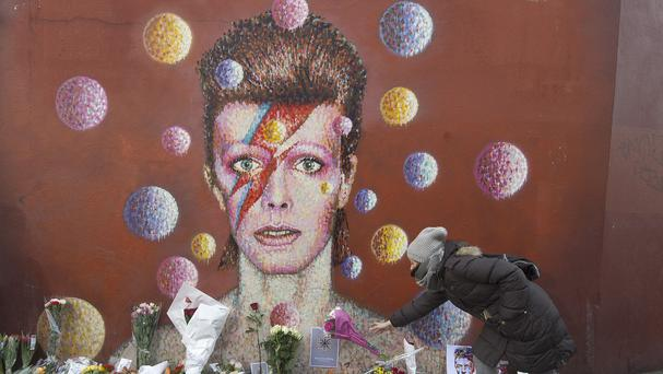 Flowers are left below a mural of David Bowie on a wall in Brixton, south London, as the top five slots on the iTunes chart were filled by his albums following his death