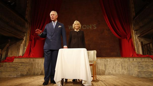 The Prince of Wales makes a speech on stage next to the Duchess of Cornwall during a visit to Wilton's Music Hall in London