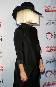 Saving face: Sia Furler refuses to play the fame game and frequently hides her features behind a mass of blonde hair