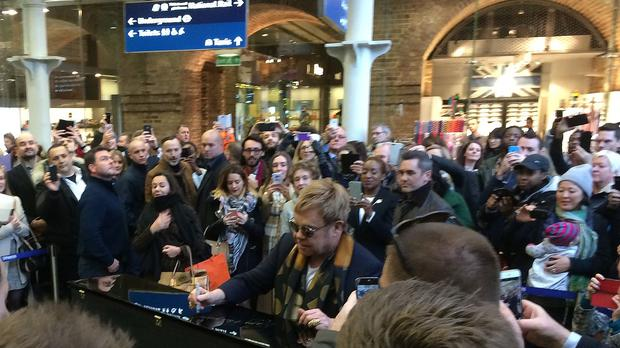 Elton John delighted commuters with an impromptu performance on a piano at London's St Pancras International station.