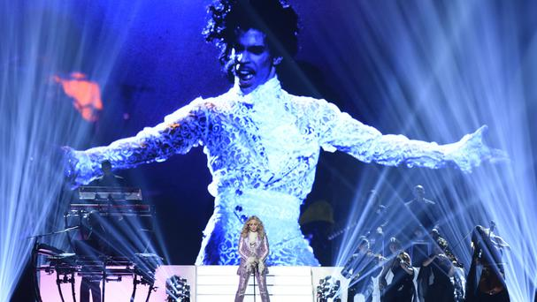 Madonna performs her tribute to Prince in front of a huge on screen image of the late star (Invision/AP)