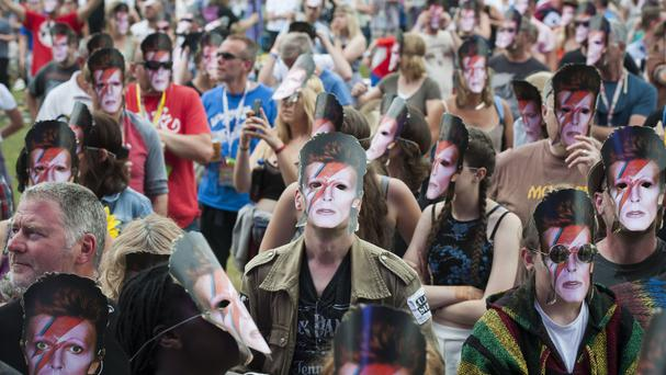 Festival-goers wear David Bowie masks during a tribute to the pop star at the Isle of Wight Festival
