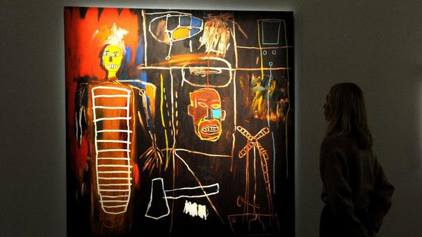 A woman looks at a painting by Jean-Michel Basquiat during the press preview of The Personal Collection of David Bowie