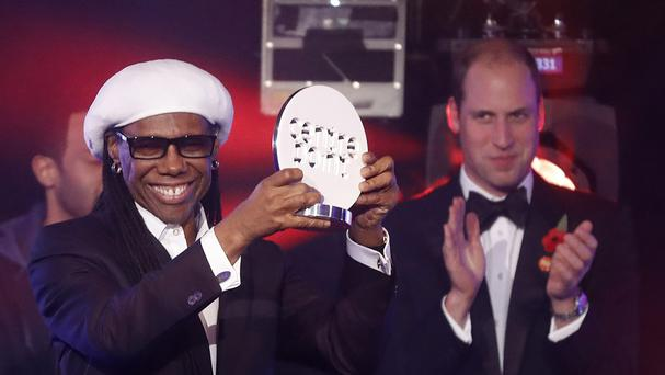 Nile Rodgers holds aloft a Centrepoint award given to him by the Duke of Cambridge