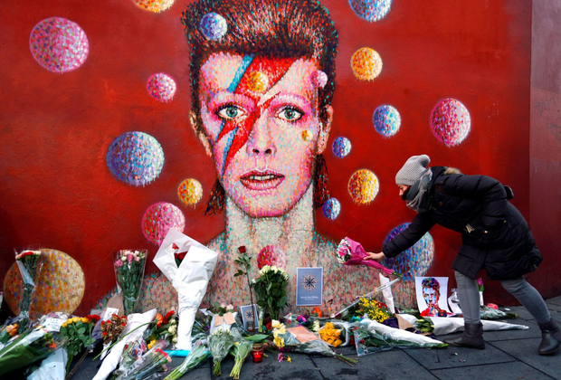 January 10, 2016: A woman leaves flowers beneath a mural of David Bowie in Brixton, London, who passed away on January 10, 2016 Photo: Getty