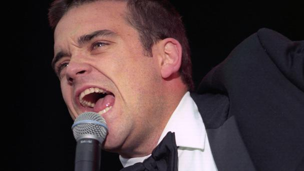 Singer Robbie Williams will perform at the Brits