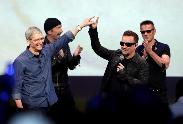 Controversy: Apple CEO Tim Cook, left, greets Bono from the band U2 after Apple Pay and U2 offered iTunes customers a free download of their latest album, Songs of Innocence in 2014. Photo: Marcio Jose Sanchez
