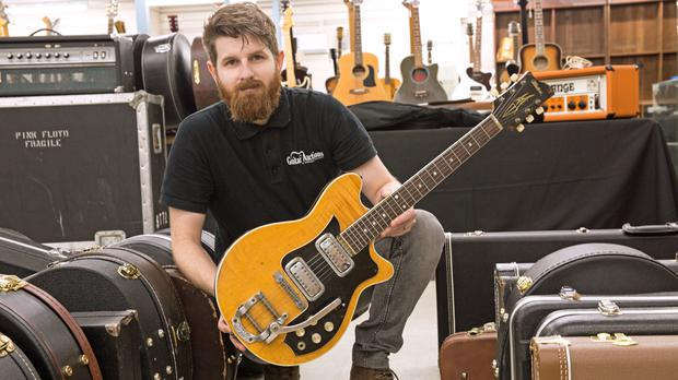 Auctioneer Luke Hobbs with George Harrison's Maton guitar (Gardiner Houlgate/PA)
