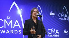 Keith Urban poses with the entertainer of the year award (Evan Agostini/Invision/AP)